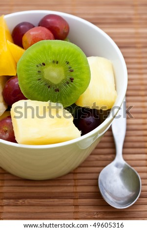 Delicious fresh fruit salad with kiwi, pineapple and grapes - stock photo