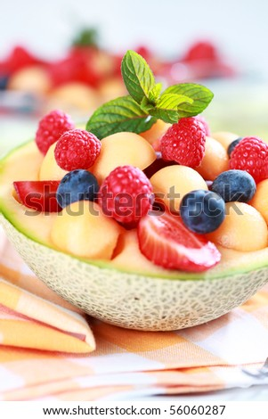 Delicious fresh fruits served in melon bowl as dessert - stock photo