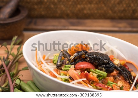Delicious fresh green papaya salad in white ceramic bowl on wooden table for local Thai food background