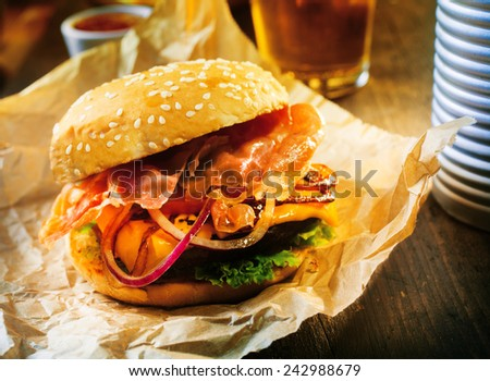 Delicious fresh hamburger or cheeseburger on a sesame bun with salad ingredients served on brown paper at a pub or bar - stock photo