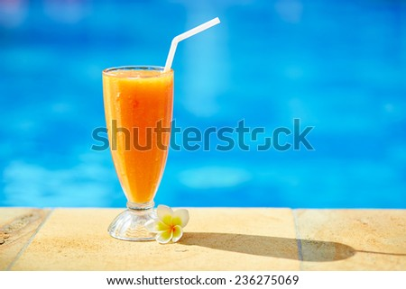Delicious fresh mango juice near the pool on a tropical resort - stock photo