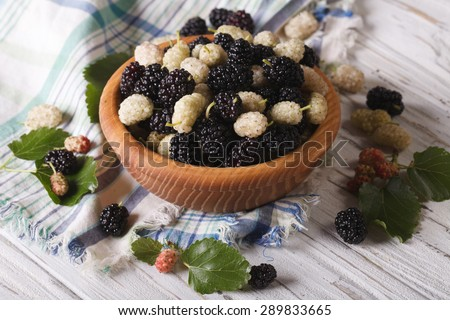 Delicious fresh mulberry in a wooden bowl on the table. horizontal - stock photo