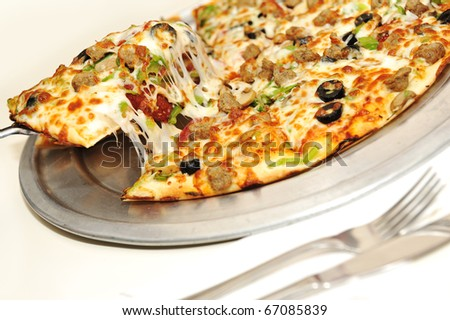 Delicious fresh pizza on table with fork and knife beside - stock photo