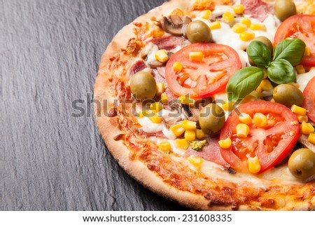 Delicious fresh pizza served on black stone - stock photo