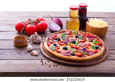 Delicious fresh pizza with ham, salami, tomato, pepper and olives served on wooden table. horizontal. selective focus, blurry background - stock photo