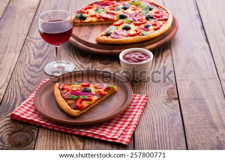 Delicious fresh pizza with ham, salami, tomato, pepper and olives served on wooden table. - stock photo
