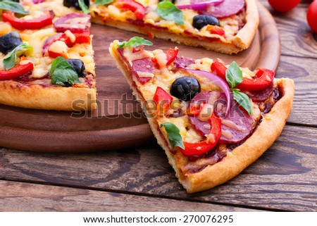 Delicious fresh pizza with ham, salami, tomato, pepper and olives served on wooden table. horizontal - stock photo