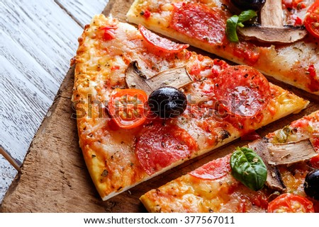 Delicious fresh pizza with mushrooms, cherry and pepperoni served on wooden table. Close-up slice tasty pizza. Mediterranean cuisine. - stock photo