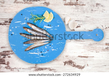 Delicious fresh sardines on wooden kitchen board with lemon, rosemary and colorful peppercorns on white textured wooden background. Culinary healthy cooking. - stock photo