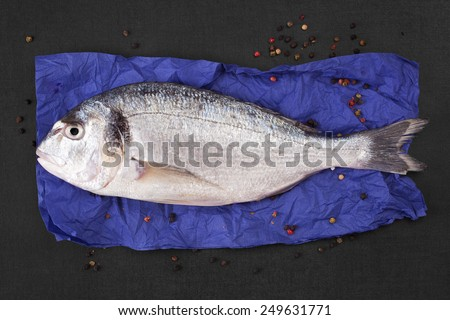 Delicious fresh sea bream fish on colorful napkin with colorful peppercorns on black textured stone table. Culinary healthy cooking. - stock photo