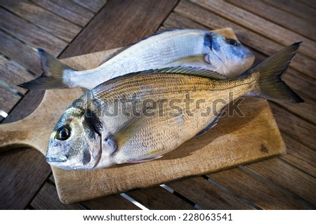 Delicious fresh sea bream fish on wooden kitchen board. Culinary healthy cooking. - stock photo