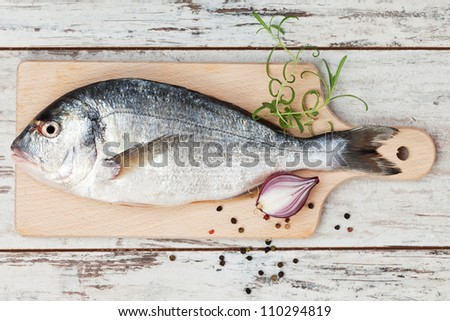 Delicious fresh sea bream fish on wooden kitchen board with onion, rosemary and colorful peppercorns on white textured wooden background. Culinary healthy cooking. - stock photo