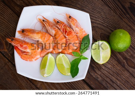 Delicious fresh seafood shrimp with lime on wooden table closeup top view horizontal - stock photo