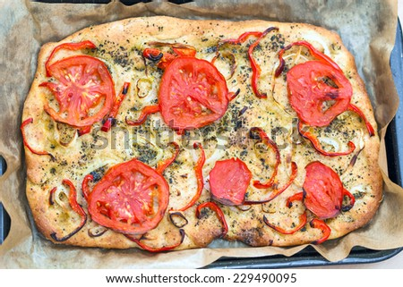 Delicious fresh traditional Italian focaccia bread with tomatoes, red peppers, onions, basil and olive oil on cooking pan - stock photo