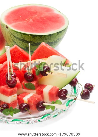 delicious fresh watermelon and melon salad with cherries and mint isolated on white - stock photo