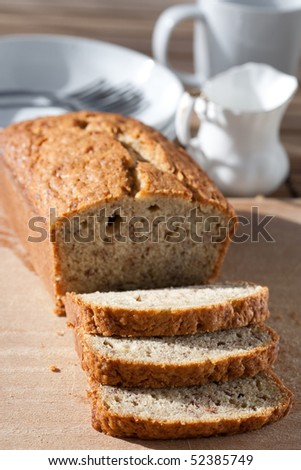 Delicious freshly baked banana bread on wooden board - stock photo