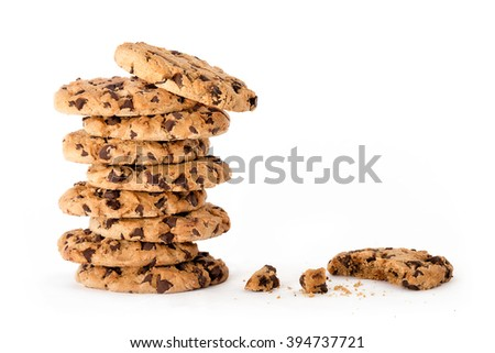 Delicious freshly baked chocolate chip cookies in a tall stack, next to a partially eaten one with crumbs isolated on white background with copy space for text - stock photo