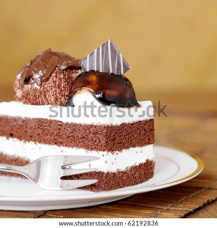 delicious freshly baked chocolate layer cake topped with cream and chocolate sauce