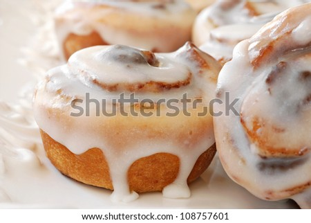 Delicious freshly baked cinnamon rolls on decorative plate.  Macro of 'mini' rolls with extremely shallow dof. - stock photo