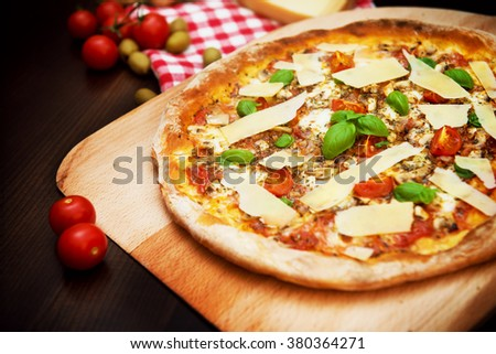 Delicious freshly baked pizza on a wooden paddle topped with tomatoes, Parmesan, basil, tomato sauce - stock photo