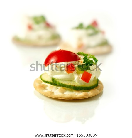 Delicious freshly prepared cream cheese canapes with cucumber, chilli peppers and tomatoes with a parsley garnish against a white background. Copy space. - stock photo
