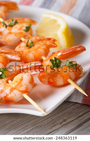 Delicious fried shrimp on wooden skewers on a plate macro. vertical  - stock photo