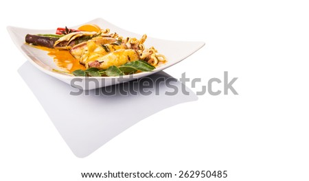 Delicious fried squid with curry gravy on white plate - stock photo