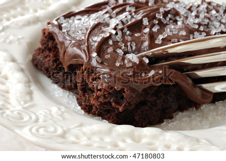 Delicious frosted chocolate brownie with sugar sprinkles and fork on decorative plate.  Macro with extremely shallow dof.