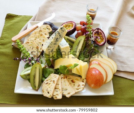 Delicious fruit and cheese platter featuring a variety of different cheeses and fresh fruits. - stock photo