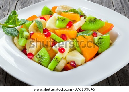 delicious fruit salad with apple, banana, kiwifruit, persimmon and pomegranate seeds in a wide rim square plate on an old wooden table, close-up, top view