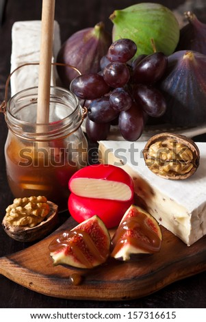 Delicious fruits, cheese and walnut with honey.