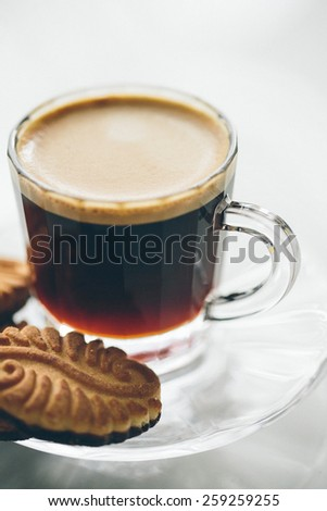 Delicious glass cup of freshly brewed frothy coffee served with a crunchy biscuit for a morning coffee break, close up view - stock photo