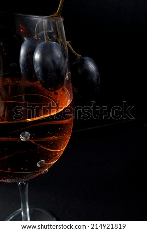 Delicious glass of wine with blue grapes in romantic light - stock photo