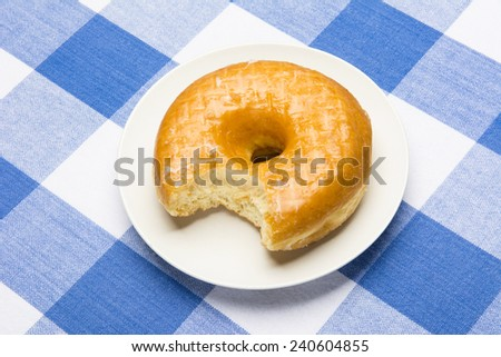 Delicious glazed donut with bite taken out during breakfast - stock photo