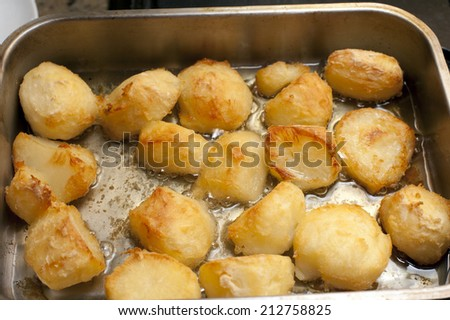 Delicious golden crispy roast potatoes in a baking tray fresh from the oven, high angle view - stock photo