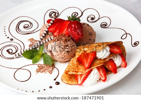 Delicious golden freshly baked strawberry and cream pancake with chocolate ice cream for a gourmet dessert - stock photo