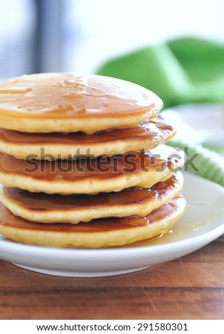 Delicious golden pancakes cooked on dry pan and served for breakfast with honey and kiwi fruit on a wooden board. Still life, copy space, selective focus, main focus on honey reflected at the side  - stock photo