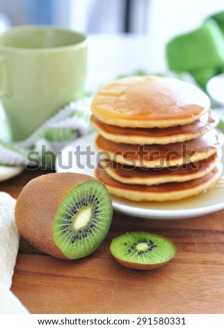 Delicious golden pancakes cooked on dry pan and served for breakfast with honey and kiwi fruit on a wooden board. Back light, still life, copy space, main focus on kiwi fruit - stock photo