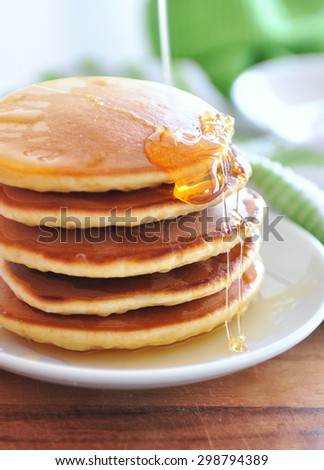 Delicious golden pancakes cooked on dry pan and served for breakfast with honey and kiwi fruit on a wooden board. Still life, copy space - stock photo