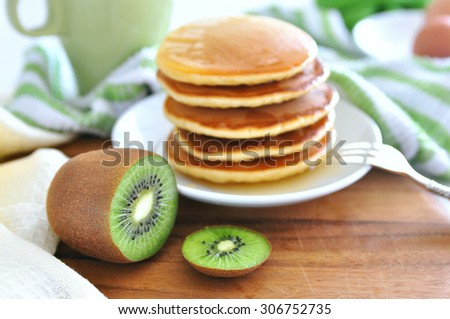 Delicious golden pancakes cooked on dry pan and served for breakfast with honey and kiwi fruit on a wooden board. Selective focus main focus on a kiwi. Healthy eating lifestyle, still life, copy space - stock photo