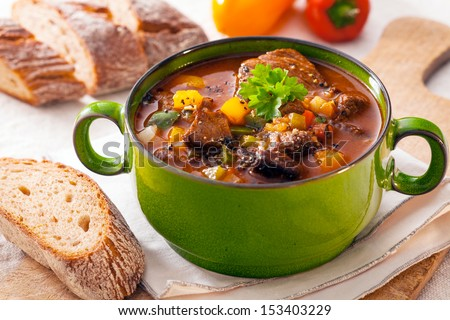 Delicious goulash casserole in a metal pot with thick rich gravy, meat and vegetables for a wholesome meal - stock photo