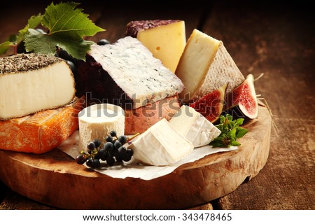 Delicious gourmet cheese platter with a wide assortment of soft and semi-hard cheeses served with sliced sweet fresh figs and grapes on a rustic wooden table with background shadow - stock photo