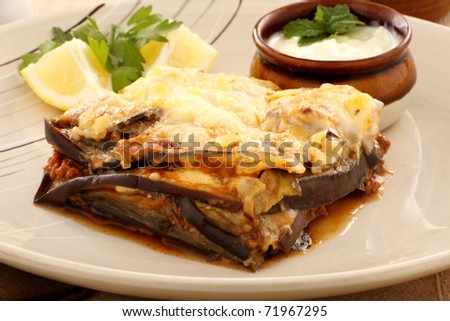 Delicious Greek moussaka with aubergine and a side garden salad. - stock photo