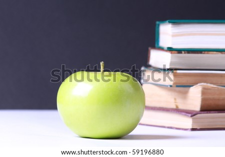 Delicious green apple against stack of books - stock photo