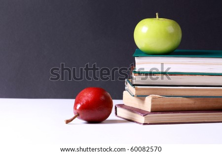 Delicious green apple and red pear with stack of books