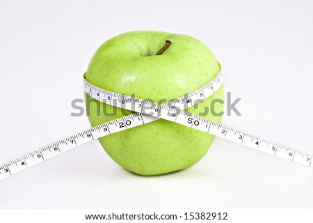 delicious green apple on white background with a  measuring tape around it. - stock photo