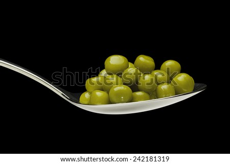 Delicious, green, canned peas in a silver spoon on a black background. - stock photo