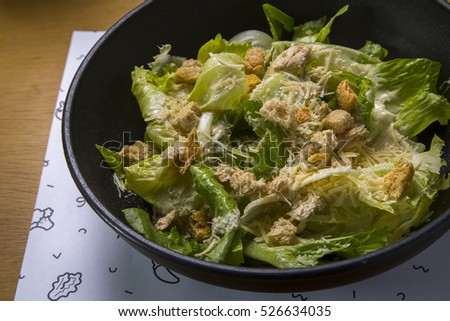 Delicious green salad with lettuce, crotons and cheese served on a black plate on a wooden table.