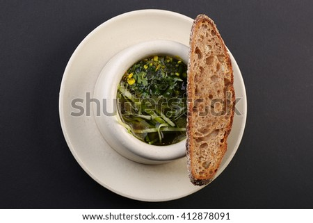 Delicious green soup with bread on black table, close-up - stock photo