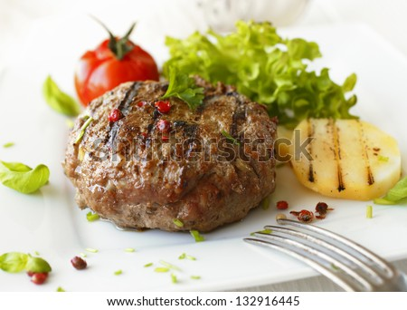 Delicious grilled beef meatball served on a white plate with tomato and lettuce with a fork in the foreground - stock photo